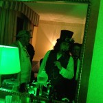 A man in a top hat looks mysteriously into a mirror bathed in green light