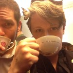 Two people face the camera, drinking from teacups